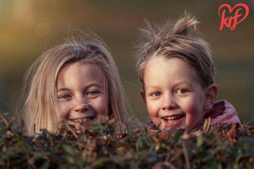 Illustrasjonsfoto av et søskenpar som titter frem bak en busk