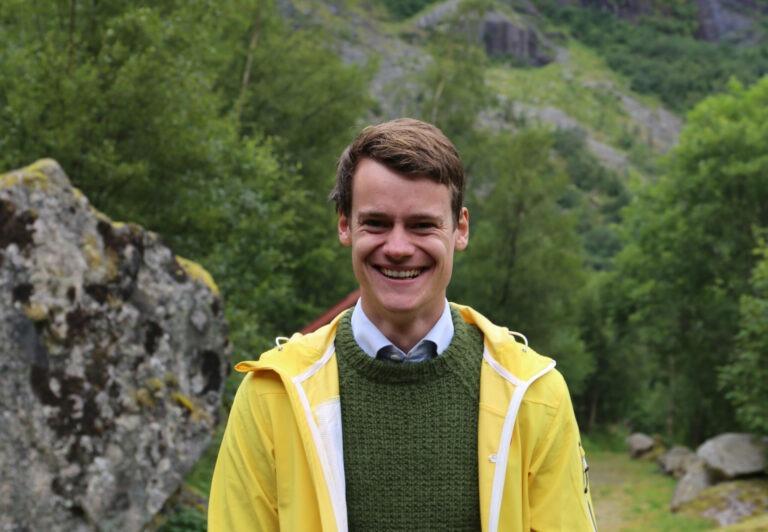 Portrett av Tore Storehaug ikledd gul regnjakke. Han smiler.