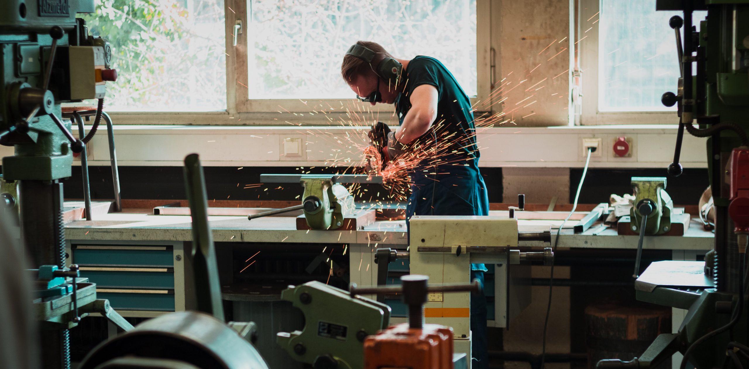 En arbeider jobber på en arbeidsbenk med å kutte stål. Det kommer gnister fra apparatet som brer seg over hele rommet. Mannen har på seg vernebriller.