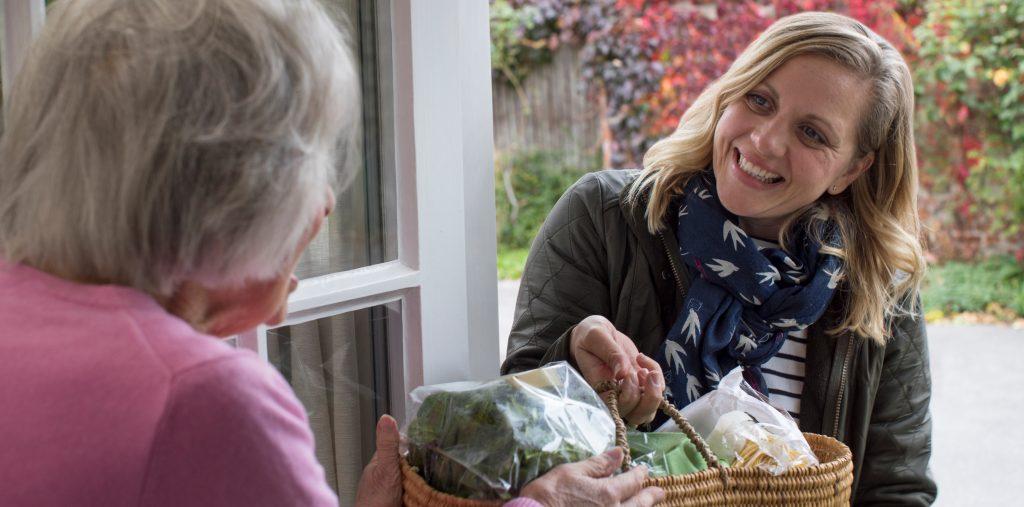 Frivillig dame deler ut mat til eldre dame