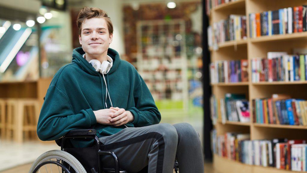 Gutt som sitter i rullestol med hodetelefoner foran en bokhylle.