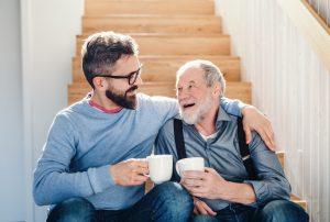 Eldre mann smiler og klemmer sin sønn. De to drikker en kopp kaffe, har på seg blå klær og sitter i en trapp.