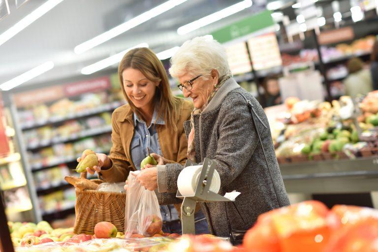 Dame hjelper en eldre dame med å handle i butikken. De to står i grønnsaksavdelingen.