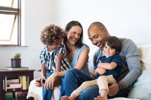 Illustrasjonsbilde av en familie som sitter i en sofa og smiler til hverandre. To sønner, en mor og en far.