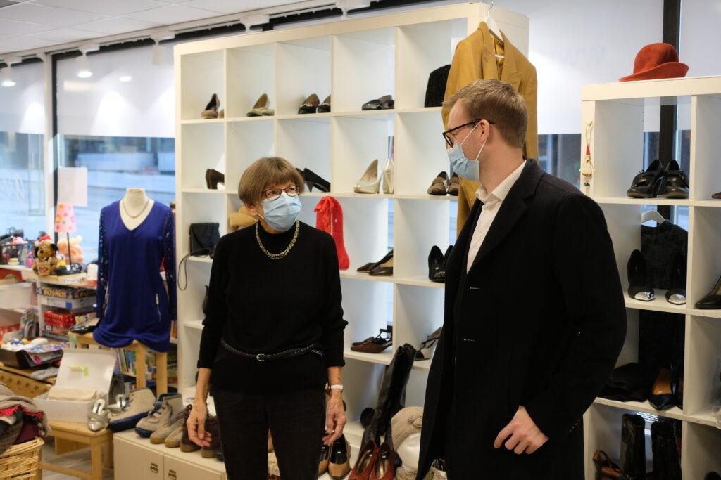 Kjell Ingolf Ropstad står ovenfor en eldre dame som heter Kirsten Hjemdal og er frivillig i Galleri Normisjon Oslo. De to står i butikken sammen.
