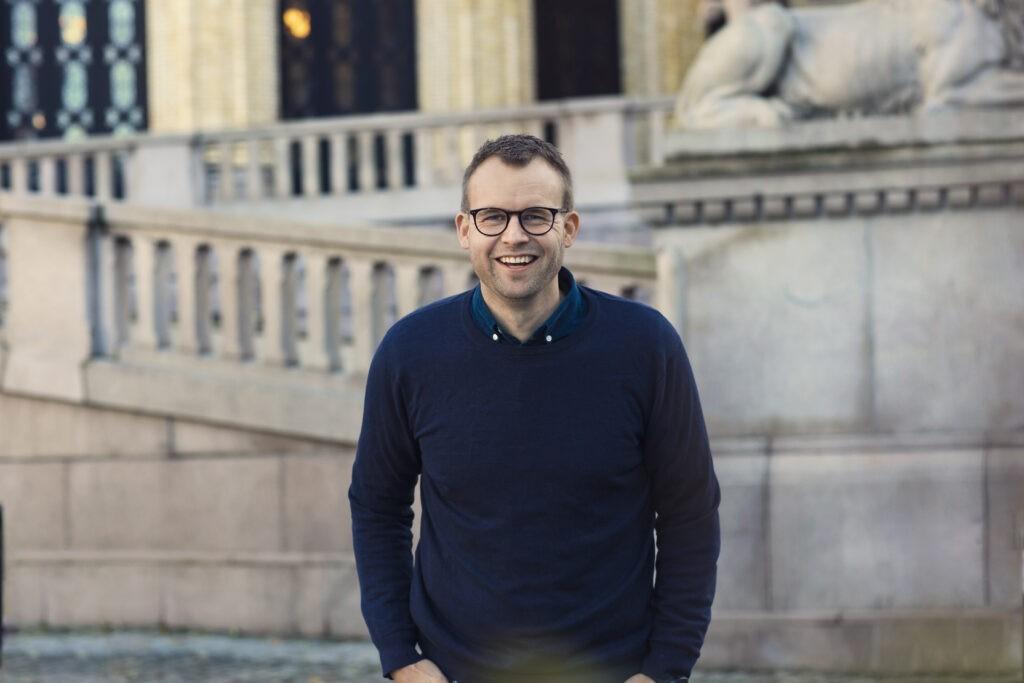 Kjell Ingolf Ropstad, barne og familieminister og partileder for Kristelig folkeparti står foran Stortinget og smiler