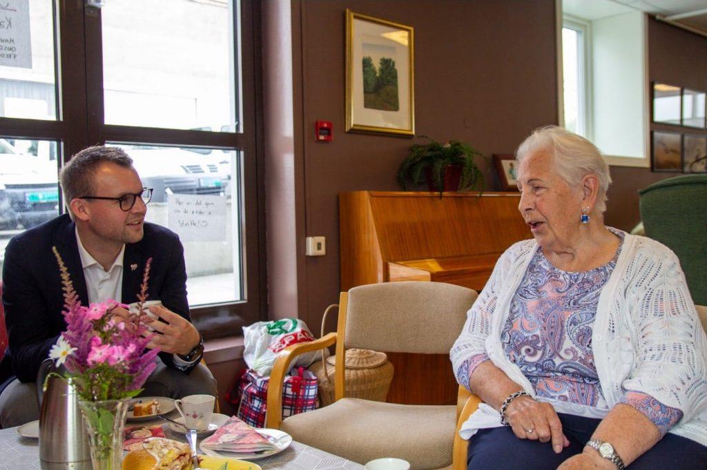 Kjell Ingolf sitter i en stol med en kaffekopp og titter bort på en eldre dame som sitter overfor ham og prater til ham.