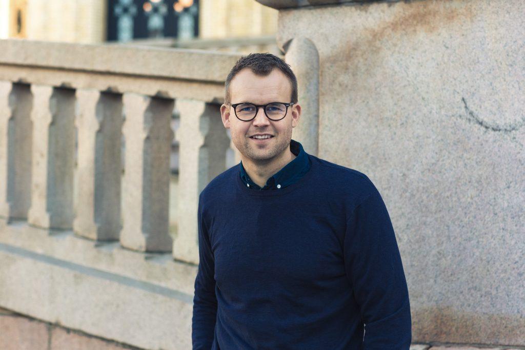 Kjell Ingolf Ropstad smiler iført genser foran Stortinget