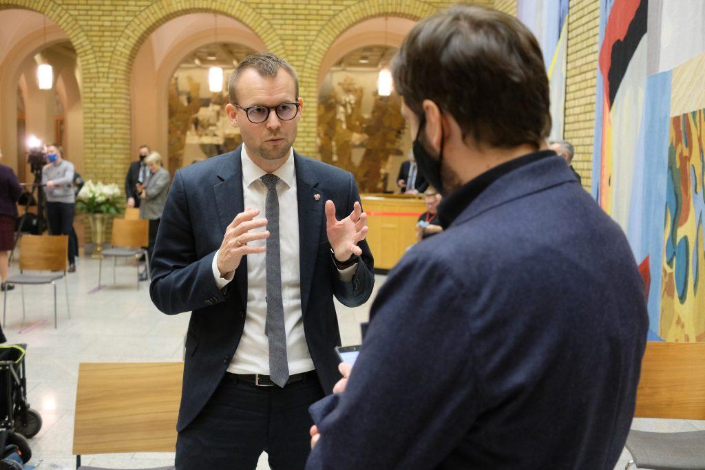 Kjell Ingolf i samtale med journalist i vandrehallen på Stortinget