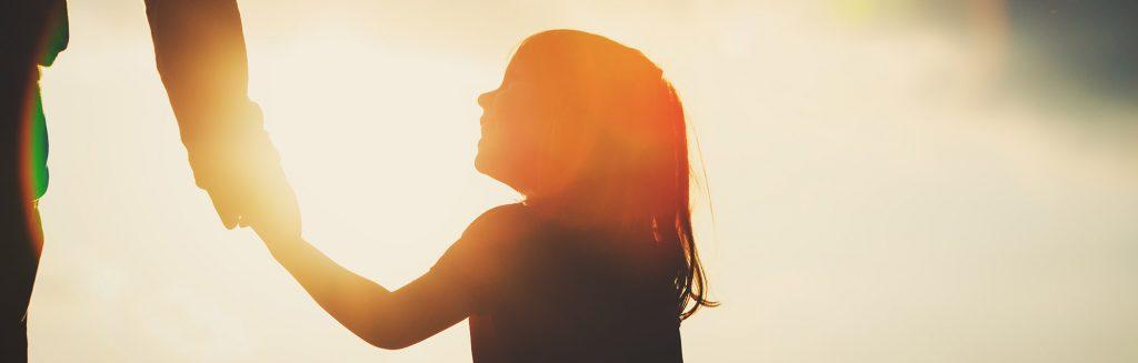Siluett av barn som holder en hånd. iStock