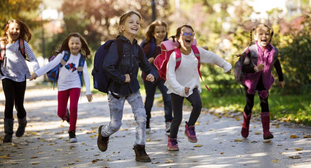 Skolestart - barn løper mot kamera og smiler med ryggsekk. Det er høst